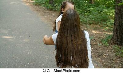 Happy little girl run to mother's hug in summer park