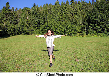 happy little girl running on green grass field