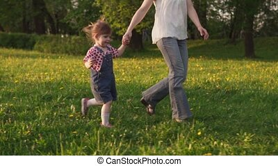 Happy little girl running with her mother on field, sunny summer day
