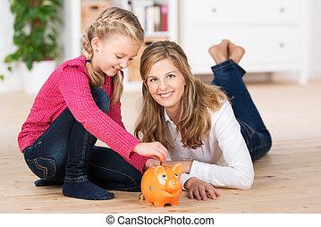 Happy little girl saving her pocket money sitting on the...