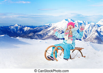 Happy little girl sit on sledge in mountains