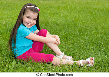 Happy little girl sits on the grass