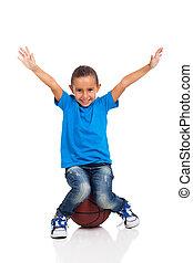 little girl sitting on a basketball ball