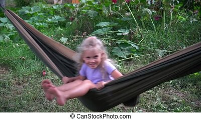 Happy little girl sitting on a hammock in summer garden. Camera motion shot with gimbal.