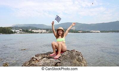 happy little girl sitting on a rock