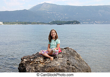 happy little girl sitting on a rock by the sea