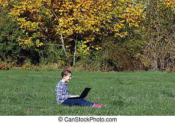 happy little girl sitting on grass and playing laptop autumn season