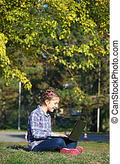happy little girl sitting on grass and playing laptop in park