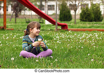happy little girl sitting on grass with ice cream