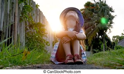 Happy little girl sitting on the grass and playing in summer garden. Outdoors. Sunset.