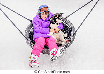 Happy little girl sitting on the swing with husky puppy dog in the winter time