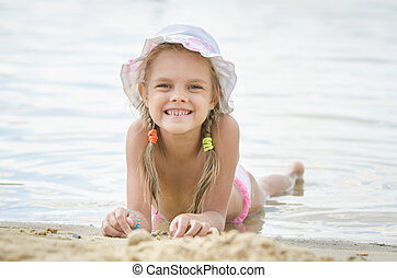 Happy little girl six years lying on the sand on the bank of the river