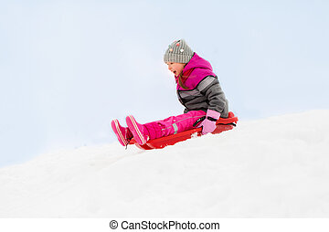 happy little girl sliding down on sled in winter