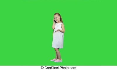 Happy little girl speaking by cell phone on a Green Screen, Chroma Key