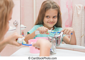 Happy little girl squeezes the toothpaste from a tube on toothbrush
