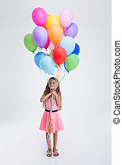 Happy little girl standing with balloons