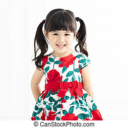 happy little girl stands on white background