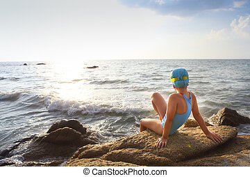 Happy little girl swimmer at the beach