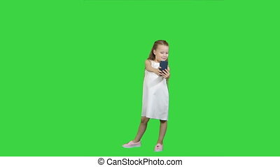 Happy little girl take a selfie with a smart phone on a Green Screen, Chroma Key