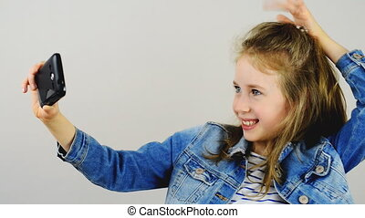 Happy little girl taking selfie with mobile phone.