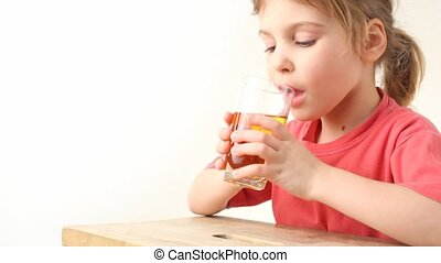 happy little girl tasting apple juice and shows thumbs up