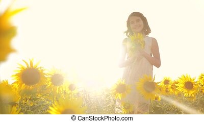 Happy little girl teen smelling a sunflower on the field in...