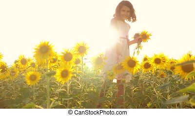 Happy little girl teen smelling a sunflower sneezes allergic...
