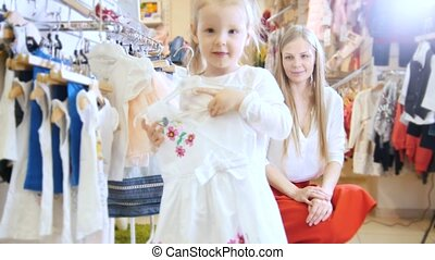 Happy little girl tries on summer dress in store