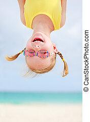 Happy little girl upside down - Adorable little girl hanging...