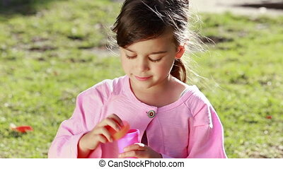 Happy little girl using a bubble wand in the countryside