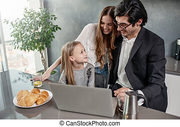 Happy little girl watching a movie on the computer with her father and mother