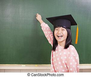 happy little girl wear a graduation hat with blackboard