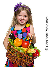 Happy little girl with a basket of vegetables