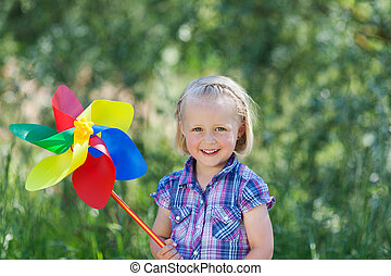 Happy little girl with a large pinwheel