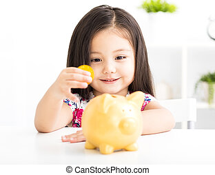 happy little girl with a piggy bank