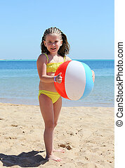 happy little girl with ball on beach