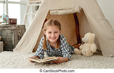 Happy little girl with book in wigwam