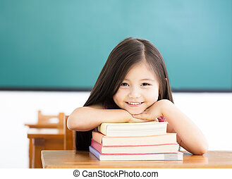 happy little girl with books in classroom