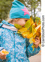 Happy little girl with bouquet of autumn leaves in the park