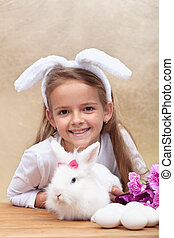 Happy little girl with bunny ears and her cute white rabbit