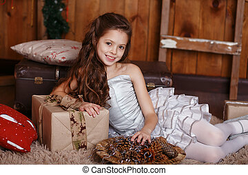 Happy little girl with Christmas gifts.