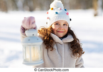 happy little girl with christmas lantern in winter
