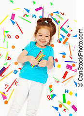 Happy little girl with colored pencils at her hand