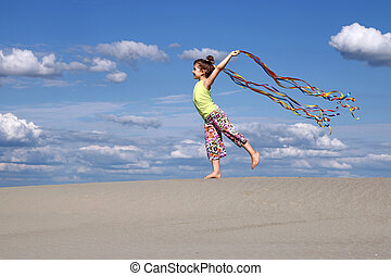 happy little girl with colorful ribbons on beach
