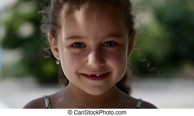 Happy little girl with curly hair, with a beautiful smile and green eyes looking at the camera, happy smiling.