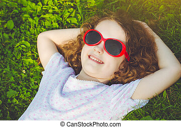 Happy little girl with glasses lying on the grass in a summer park. Happy childhood concept.