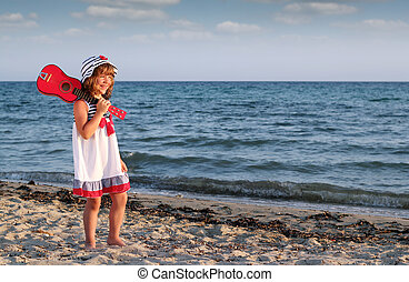 happy little girl with guitar on beach