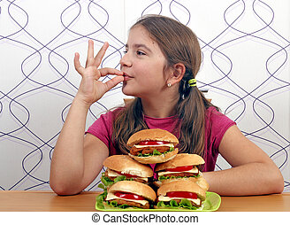 Happy little girl with hamburgers and ok hand sign