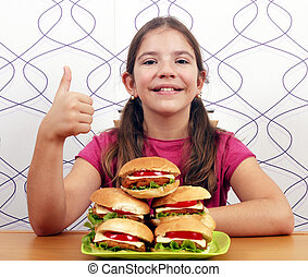 happy little girl with hamburgers and thumb up