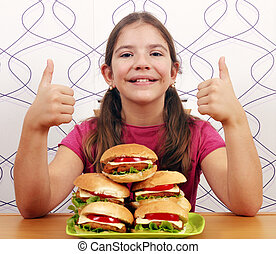 Happy little girl with hamburgers and thumbs up